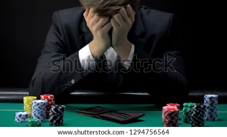 Young devastated businessman losing poker game at casino, gambling addiction Royalty-Free Stock Photo #1294756564