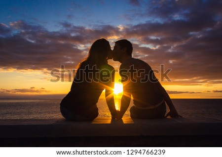 Man and woman sitting by the sea kiss at sunset at Meloneras beach walk, Gran Canaria. Couple silhouette enjoying colorful twilight. Valentines Day, honeymoon romantic date concepts #1294766239