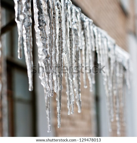 icicles which are hanging down from a roof. Royalty-Free Stock Photo #129478013