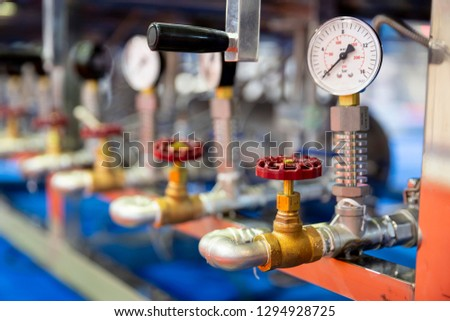 Pressure measuring instrument - bar, psi. Red metal valves on the pipes. Pressure device for industry system. #1294928725