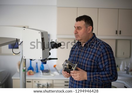 Young Man Repairing Medical Device in Dentist Office #1294946428
