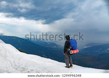 Man with backpack trekking in mountains. Cold weather, snow on hills. Winter hiking #1294996348