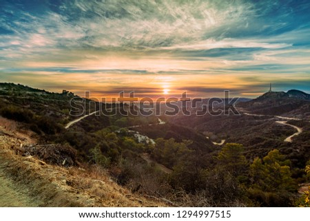 An orange sunset view across the horizon between hills and mountains from a distant mountain top view in Los Angeles, California. #1294997515