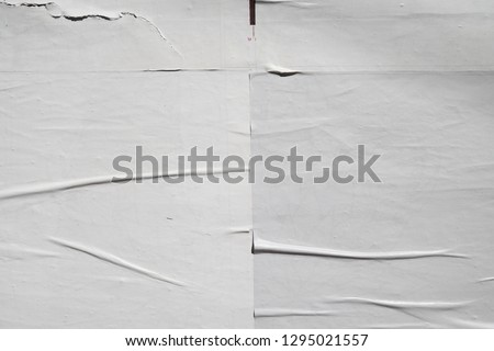 creased crinkled lined overlaying layers of white posters #1295021557