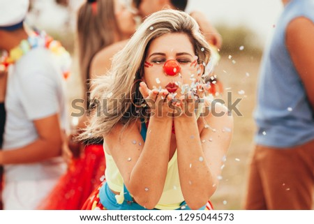 Brazilian Carnival. Young woman in costume enjoying the carnival party blowing confetti #1295044573