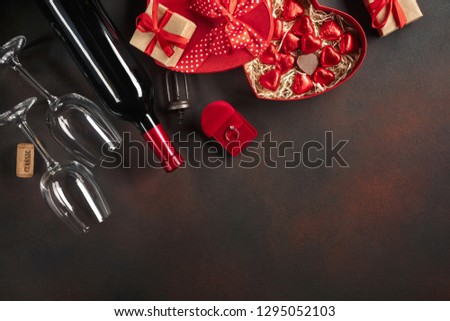 Valentine's Day with hearts, wine, corkscrew, glasses, gifts, a heart-shaped box and a blackboard. Top view with copy space #1295052103