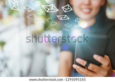 Woman hand using smartphone with email  icon pop up recieve and send notification on screen of mobile phone. Business communication technology concept. #1295095165