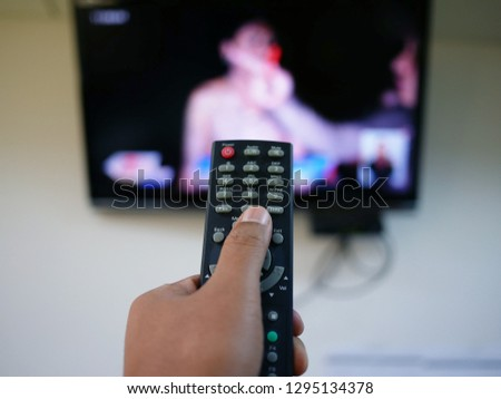 closeup of hand with the remote control television and presses the button. #1295134378