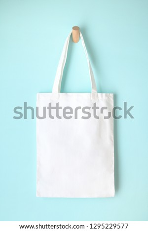white blank tote bag mock up design on blue background hanging on wooden hanger #1295229577