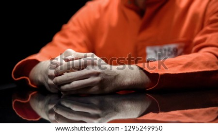 Hand of male prisoner, inmate giving evidence in detention room, cooperation #1295249950