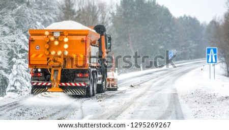 Snow plow on highway salting road. Orange truck deicing street. Crystals dropping on snowy asphalt. Maintenance winter vehicle in action. #1295269267