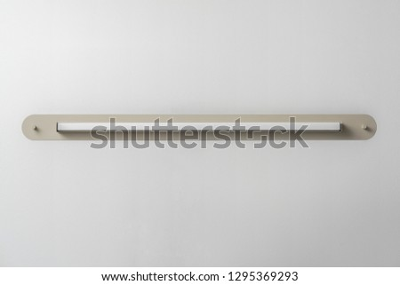 Trendy metal beige LED lamp on the gray wall background indoors. Closeup horizontal photo. #1295369293