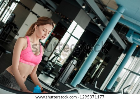 Young woman in gym healthy lifestyle standing on treadmill looking down breathing tired #1295371177