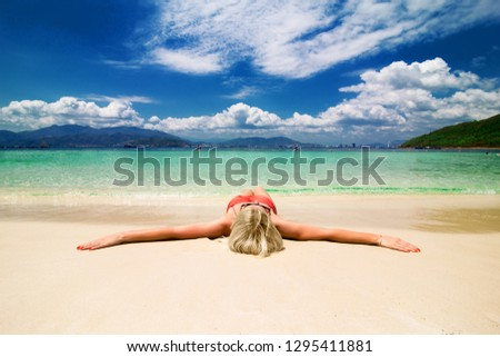 Girl lies on the white sand on the beach. Woman in bikini with outstretched arms on paradise beach. Travel card with perfect getaway. Paradise tropical vacation. Luxury living lying down sun tanning