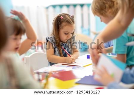 Group of children drawing with nursery teacher in kindergarten #1295413129