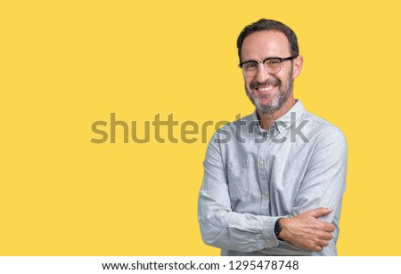 Handsome middle age elegant senior man wearing glasses over isolated background happy face smiling with crossed arms looking at the camera. Positive person. #1295478748
