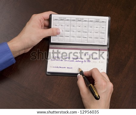 Woman writing check to credit card company #12956035