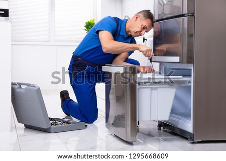 Mature Male Serviceman Repairing Refrigerator With Toolbox In  Kitchen #1295668609