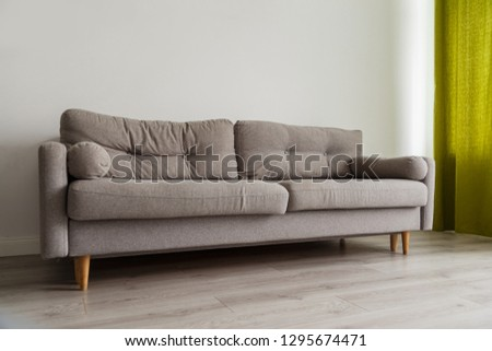 Grey sofa in monochromatic living room with green curtains #1295674471