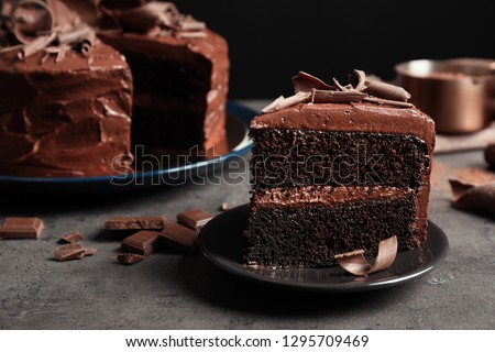 Plate with slice of tasty homemade chocolate cake on table Royalty-Free Stock Photo #1295709469