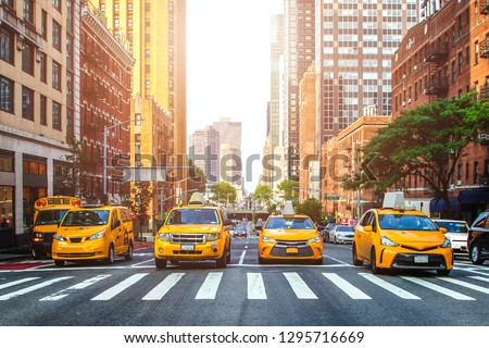 Yellow cabs waiting for green light on the crossroad of streets of New York City during sunny summer daytime #1295716669