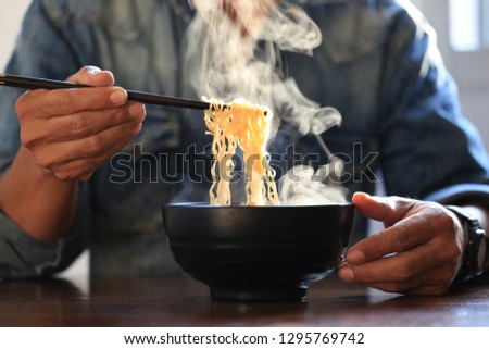 Man hand holding chopsticks of instant noodles in wood bowl with smoke rising in the home, Sodium diet high risk kidney failure, Healthy eating concept  #1295769742