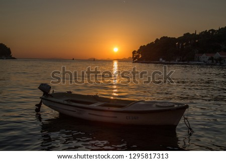 Cavtat, Croatia - July 3 2016: Sunset in Cavtat with a boat in the foreground #1295817313