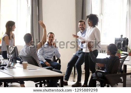 Diverse team in coworking space voting some colleagues agree raises hands. Positive black leader woman with creative group of businesspeople discussing sharing ideas together in office at meeting #1295889298