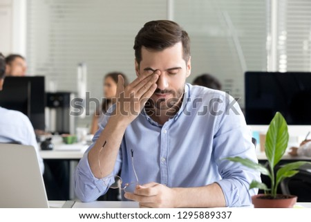 Office worker sitting at desk taking off glasses rubbing massaging eye tired of working at computer having blurry vision problem and dry eyes after long use of laptop, suffering from eyestrain at work #1295889337