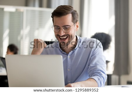 Excited worker sitting at desk in coworking space use computer reading message looking at device screen received great unbelievable opportunity or reward. Motivated employee celebrating job promotion #1295889352