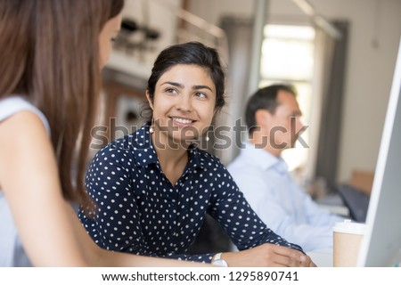 Friendly smiling indian employee female listen colleague girl sitting together at desk in office. Diverse workers talking discussing sharing ideas having busy workday. Manager or mentor teach intern #1295890741