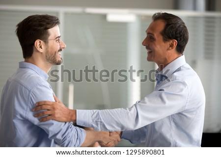 Businessmen standing smiling shaking hands greeting congratulating each other at business meeting. Millennial office workers handshaking during acquaintance expressing trust support and collaboration Royalty-Free Stock Photo #1295890801