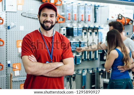 Confident smiling salesman on foreground in power tools store. Guy is ready to help clients on background. #1295890927