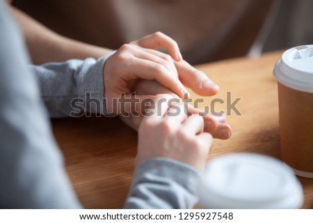Close up couple in love sitting in cafe together, holding hands, young girlfriend and boyfriend on first date, good relations, trusted friends meeting in public place together, true friendship #1295927548