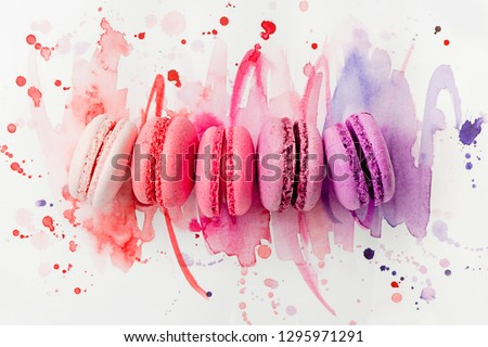 A row of bright macarons of different color on a watercolor background. Pastel colors with a gradient. Art of patisserie concept. #1295971291