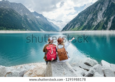 Travelers couple look at the mountain lake. Travel and active life concept with team. Adventure and travel in the mountains region in the Austria. Travel - image #1295988178