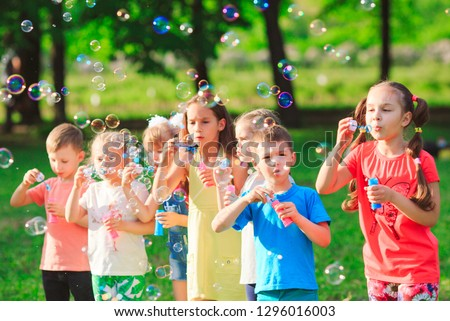 Group of children blowing soap bubbles #1296016003