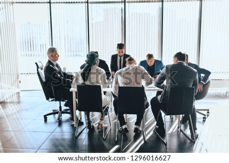 divered business people gathered to discuss some important problems in the office with modern interior and panorama window #1296016627