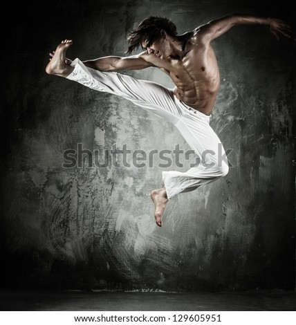 Young b-boy man with naked torso performing jumps #129605951
