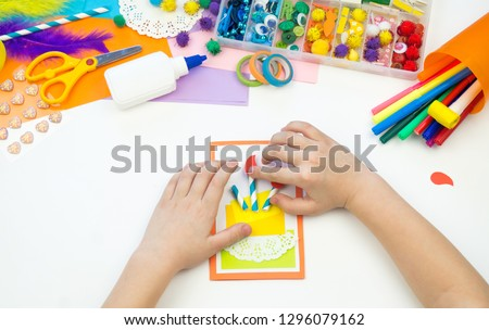 Child makes a postcard with a picture of a cake. Kid paperwork. Material for creativity. Kindergarten and school.