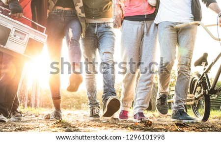 Friends walking in city park with backlight and sunflare halo - Millenial friendship concept and multiracial young people on alternative fashion having fun together - Leg view with soft blurred motion #1296101998