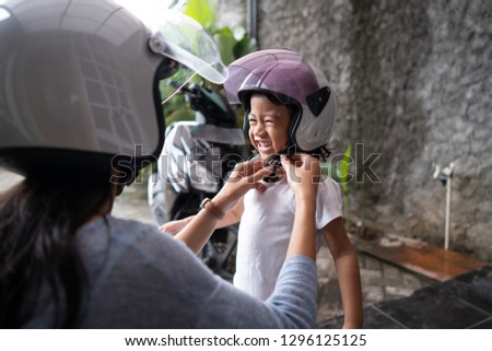 beautiful mother help her child to put on a helmet. safety first before riding a motorbike #1296125125