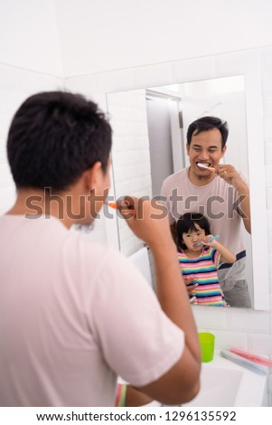 asian father and daughter brushing teeth together in bathroom before bed #1296135592