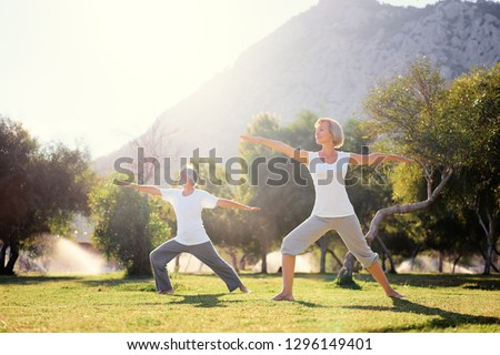 Yoga at park. Senior family couple exercising outdoors. Concept of healthy lifestyle. #1296149401