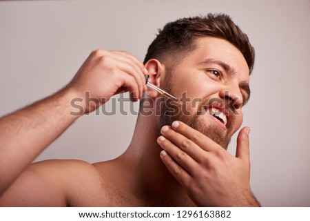 Close-up image of handsome man holding pipette with oil for beard Royalty-Free Stock Photo #1296163882