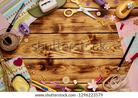 Tools for scrapbooking on the wooden background. Copy space in the middle. Royalty-Free Stock Photo #1296223579