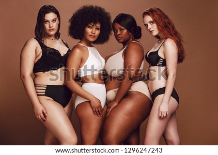Group of different size women in lingerie looking at camera. Multi-ethnic women in different under garments posing together in studio. #1296247243