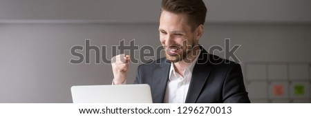 Horizontal photo happy businessman in suit sitting at desk look at laptop read receive great news online celebrate success win result concept, banner for website header design with copy space for text Royalty-Free Stock Photo #1296270013