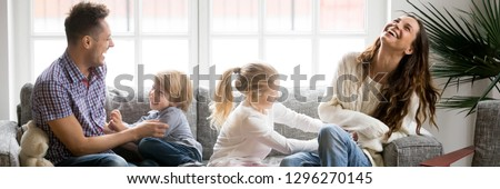 Horizontal photo kids tickling parents happy full family have fun sitting on sofa in living room leisure activities spend time at home concept banner for website header design with copy space for text