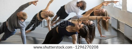 Group of millennial sporty girls and guys doing yoga Vasisthasana exercise, stretching in Side Plank pose. Active healthy wellbeing lifestyle concept. Horizontal photo banner for website header design #1296270208